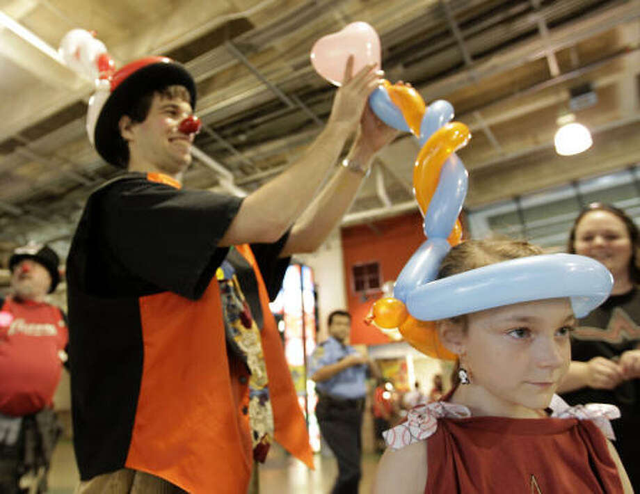 Erica Walker, 6, gets her balloon hat from JoJo the Clown during Fan Fest. Photo: Karen Warren, Chronicle