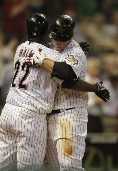 Brett Wallace hugs Bill Hall after hitting a solo home run during the ninth inning.