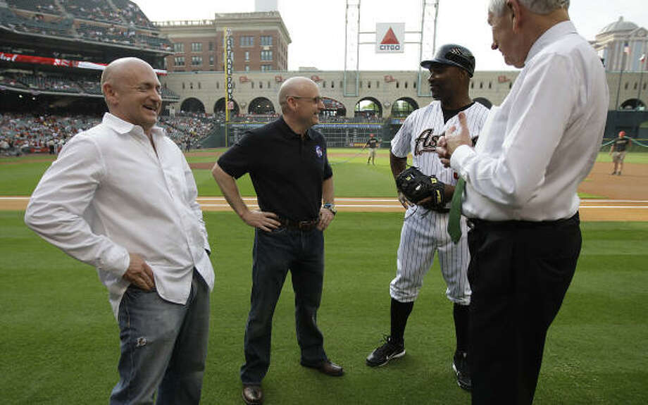 Astronauts Mark Kelly, left, and his brother, Scott Kelly, chat with Astro Dave Clark and owner Drayton McLane before the start of the game. Photo: Karen Warren, Chronicle