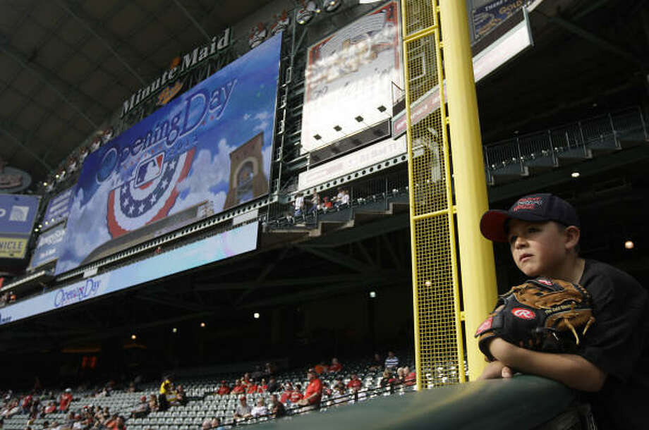 Joshua Rivas, 7, of Houston, waits to catch a ball with the giant scoreboard in the background during batting practice. Photo: Karen Warren, Chronicle