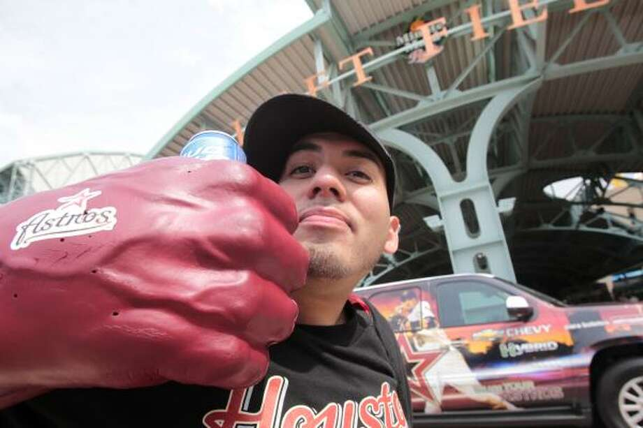 Astros fan Rudy Gutierrez holds up his Astros Hulk fist as he enjoys the Tenth Annual Opening Day Street Festival outside Minute Maid Park in Houston, Texas. The Houston Astros are matching up with the Florida Marlins in their home opener. Photo: Billy Smith II, Chronicle