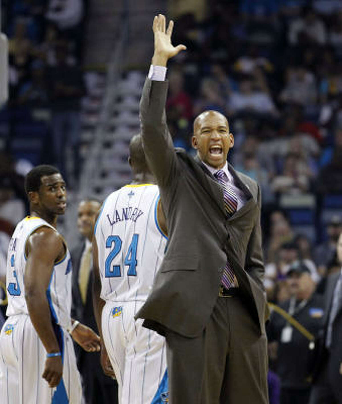 Hornets head coach Monty Williams complains to the referees as point guard Chris Paul (3) and power forward Carl Landry (24) walk off the court during a timeout.