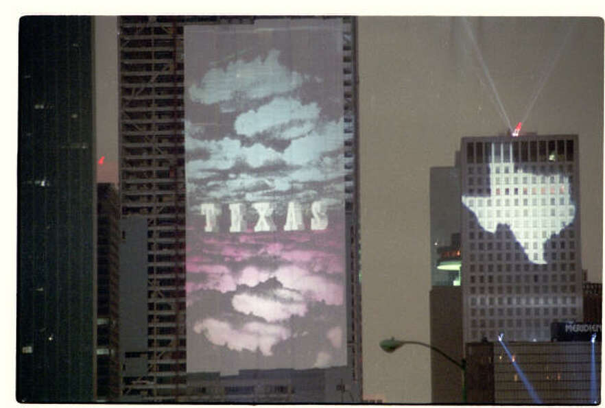 An image celebrating Texas is projected onto the Heritage Plaza building for