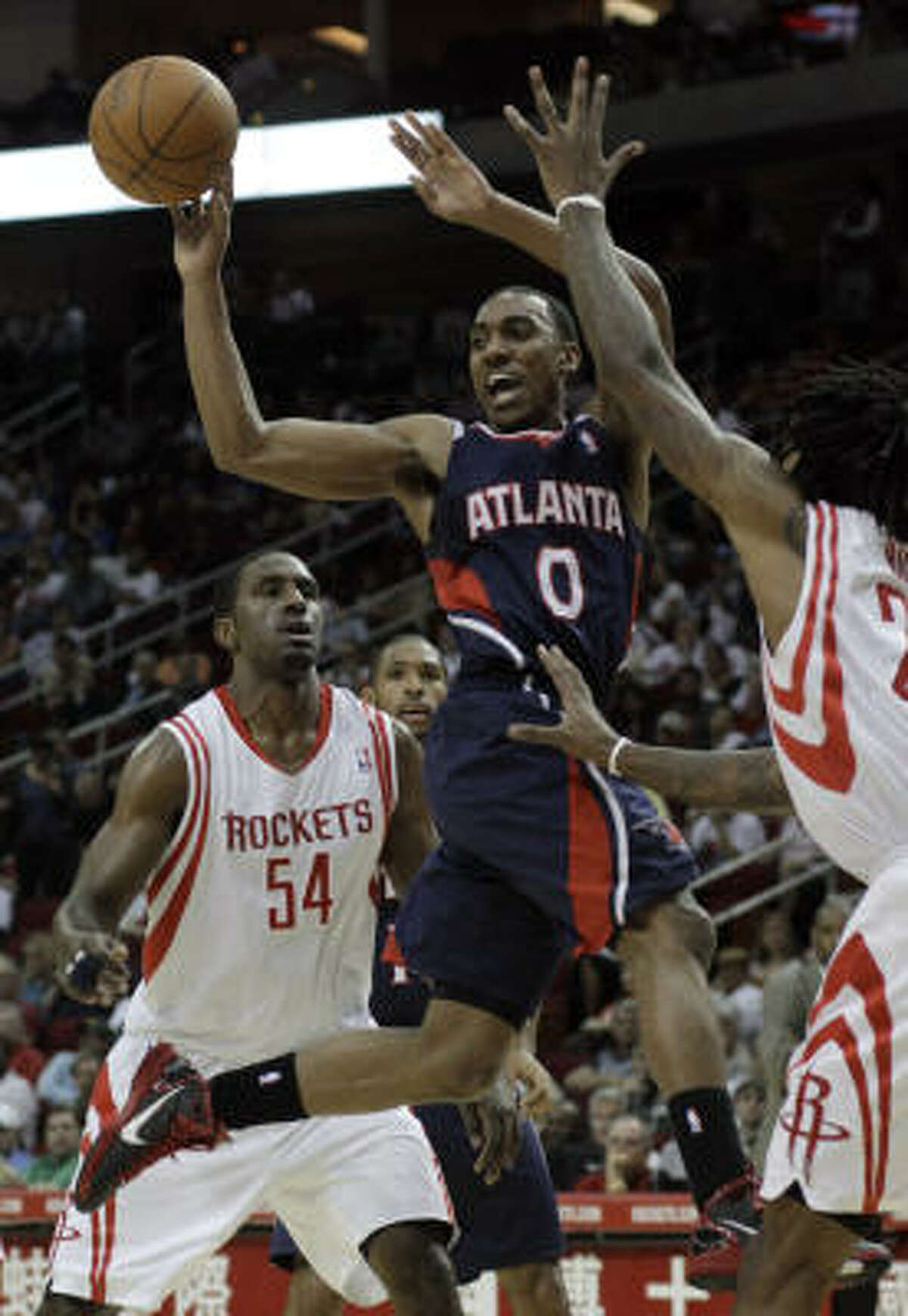 Hawks guard Jeff Teague (0) goes up between Rockets power forward Patrick Patterson (54) and forward Jordan Hill in the first half.