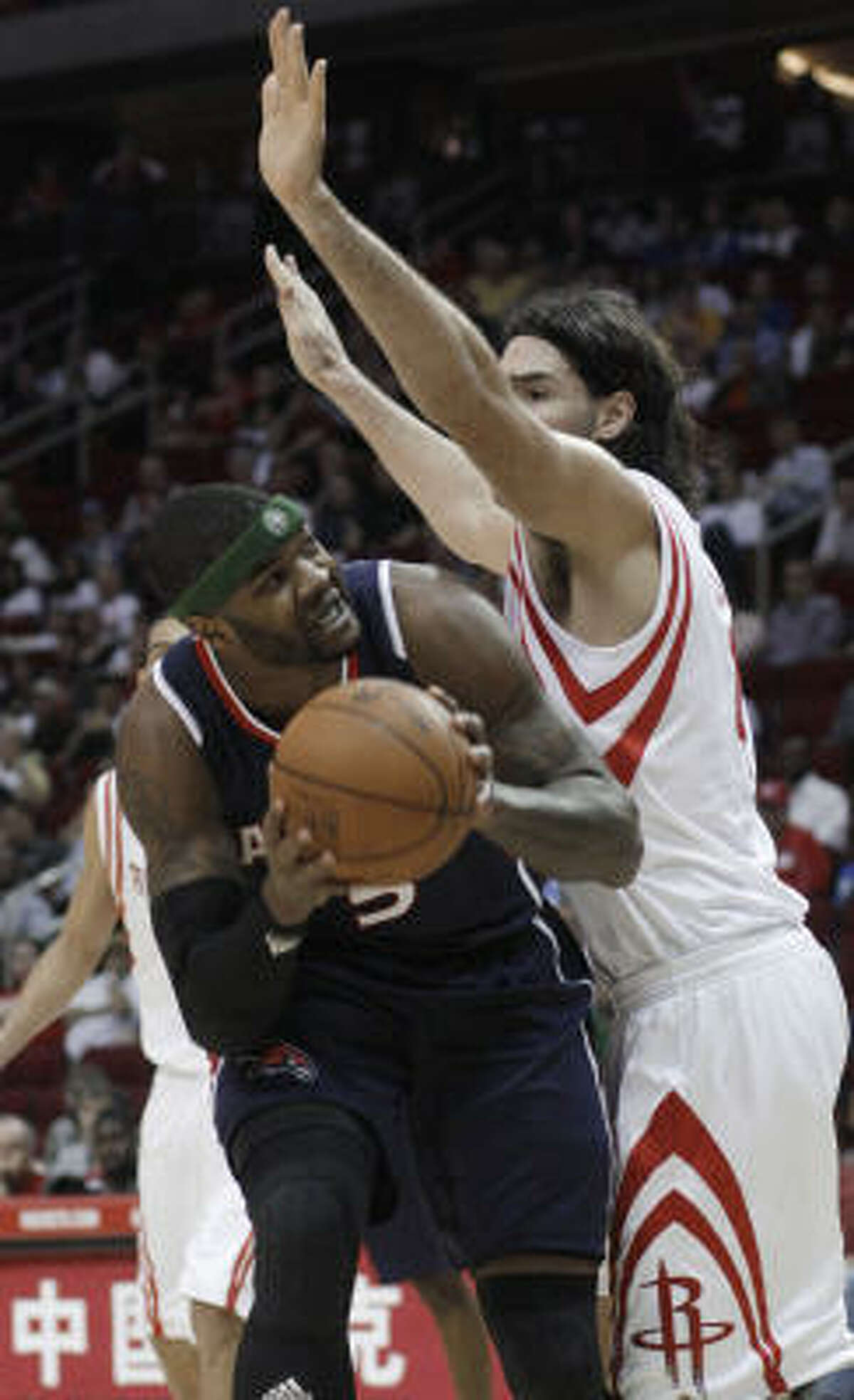 Hawks forward Josh Smith, left, looks to get past Rockets forward Luis Scola in the first half.