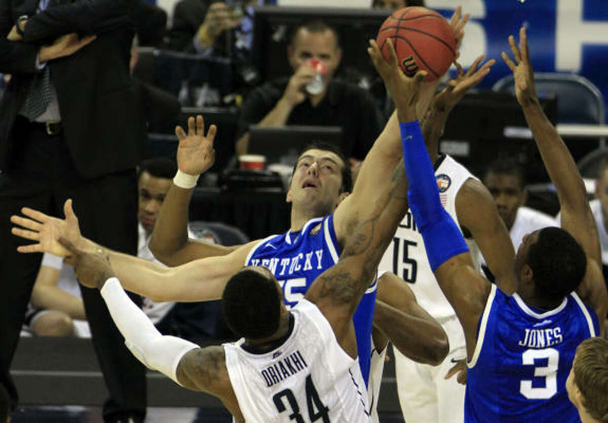 Kentucky forward Josh Harrellson (55) and Kentucky forward Terrence Jones (3) battle for a rebound against Connecticut center Alex Oriakhi (34).