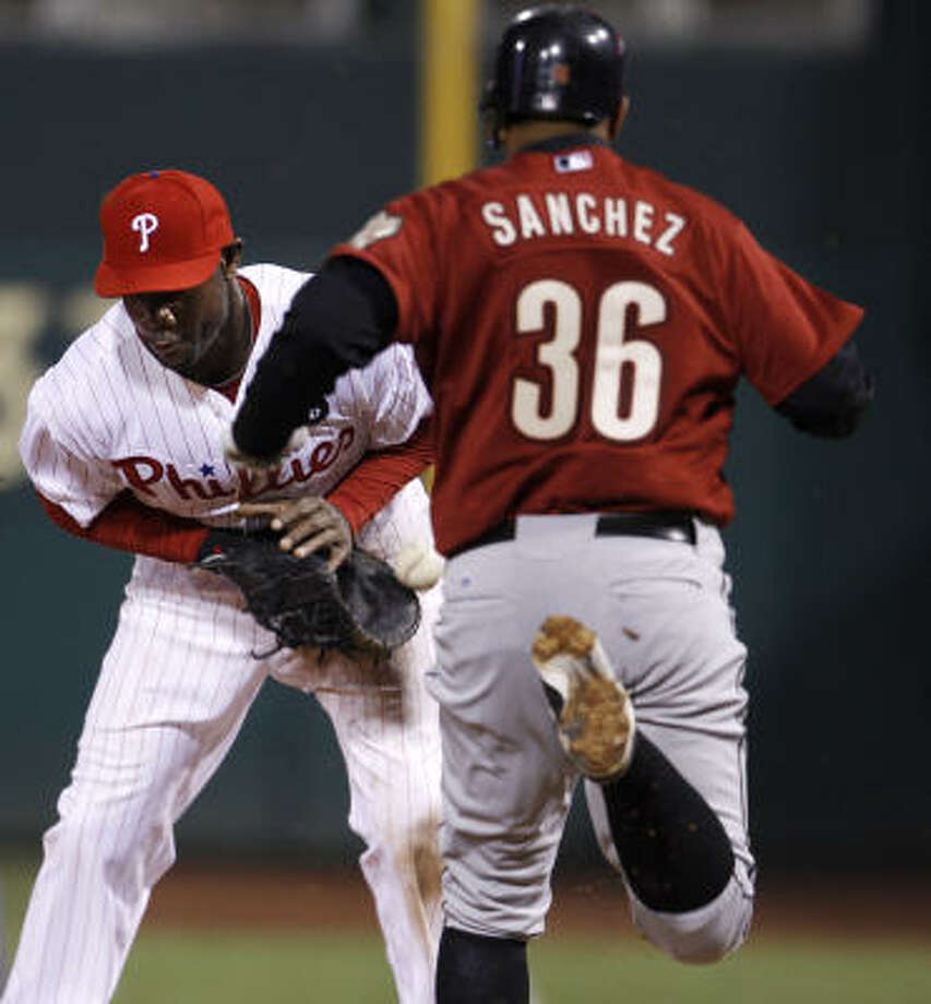 Philadelphia Phillies first baseman Ryan Howard, left, can't handle the throw from third baseman Placido Polanco, not pictured, as Houston Astros' Angel Sanchez runs to first in the eighth inning of a baseball game, Saturday, in Philadelphia. Sanchez was safe at first on the throwing error by Polanco. Philadelphia won 9-4. Photo: Matt Slocum, AP