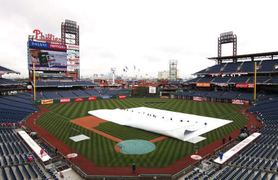 Members of the grounds crew remove the tarp from the field  before the start of the opening day game. Photo: Rob Carr, Getty Images
