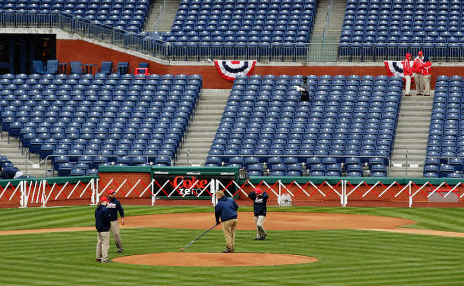 Members of the grounds crew groom the pitchers mound before the start of the opening day game. Photo: Rob Carr, Getty Images
