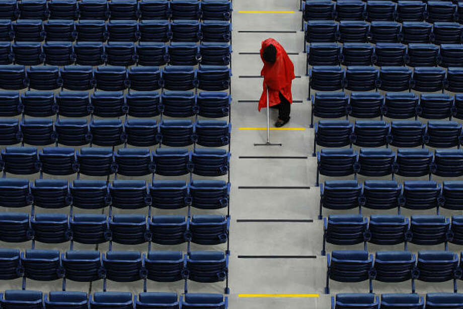 A stadium worker clears standing-water  from the isles before the opening day baseball game between the Philadelphia Phillies and the Houston Astros. Photo: Matt Slocum, AP