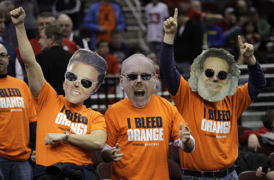 Fans Chris Groat, left, John Groat, and Denis Hickey, wears masks of Elvis, Jim Boeheim and Jerry Garcia, cheer before the third-round game between Syracuse and Marquette. Photo: Tony Dejak, AP