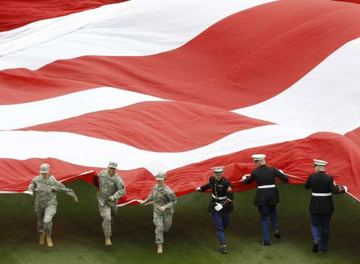 Member of the armed forces unfurl a giant U.S. flag before the opening day baseball game between the Philadelphia Phillies and the Houston Astros in Philadelphia.