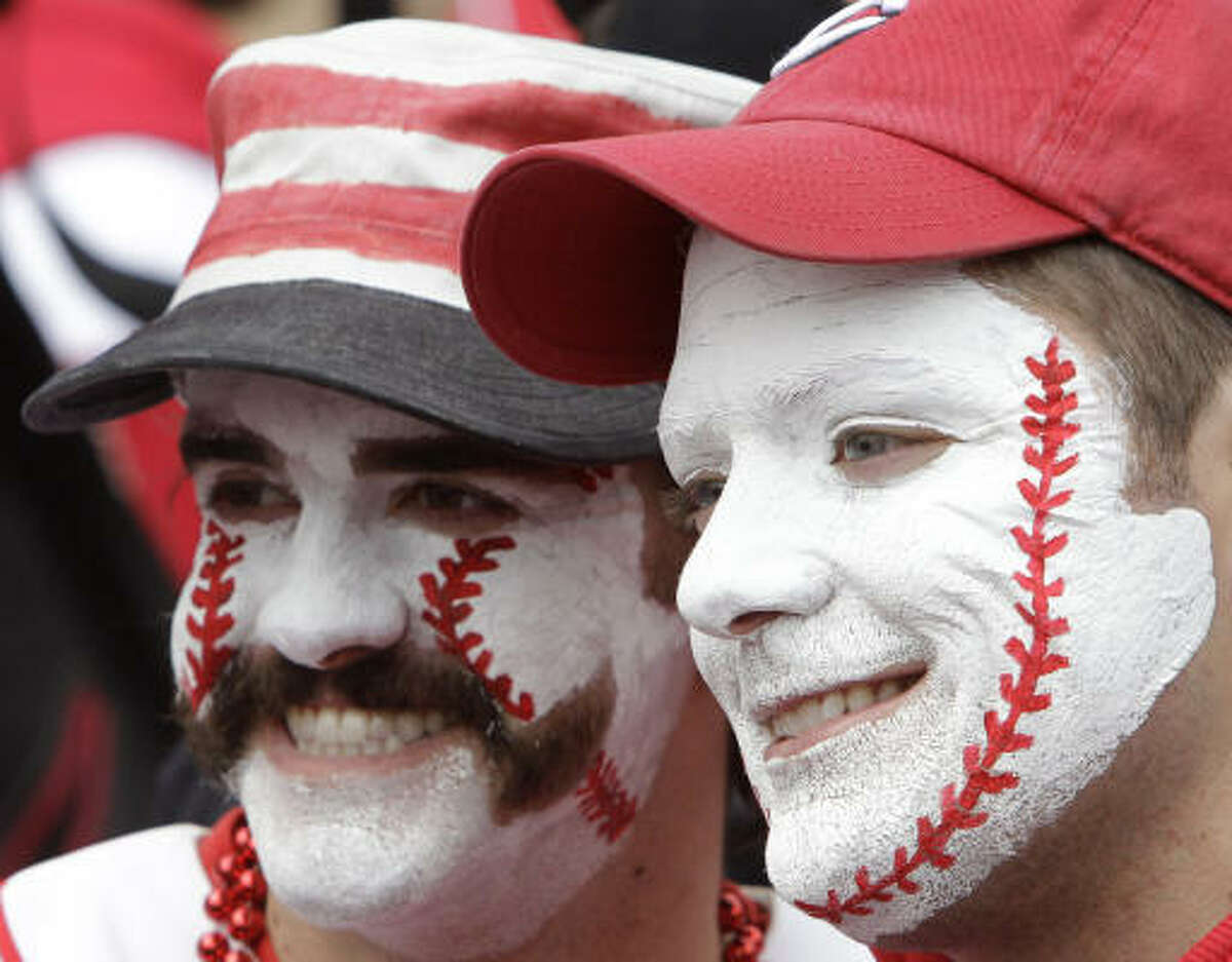 Cincinnati Reds fans Kyle Hackenberg, left, and Eric Myers pose for pictures for another fan during batting practice before the Reds opening day baseball game against the Milwaukee Brewers in Cincinnati.