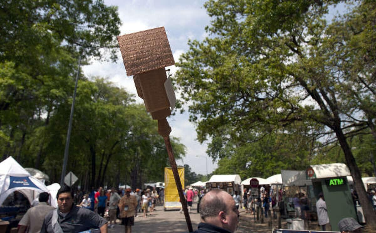 A man walks through the Bayou City Art Festival with a newly purchased birdhouse.
