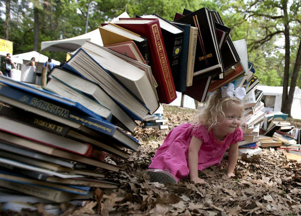 Lucy Simmons crawls under a book exhibit at the Bayou City Art Festival in Houston.