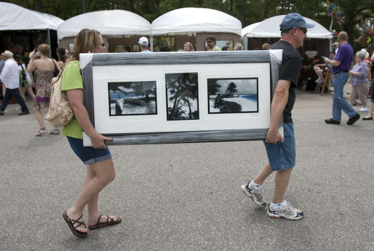 Colleen and Tim Neal carry their newly purchased painting as they leave the Bayou City Art Festival.