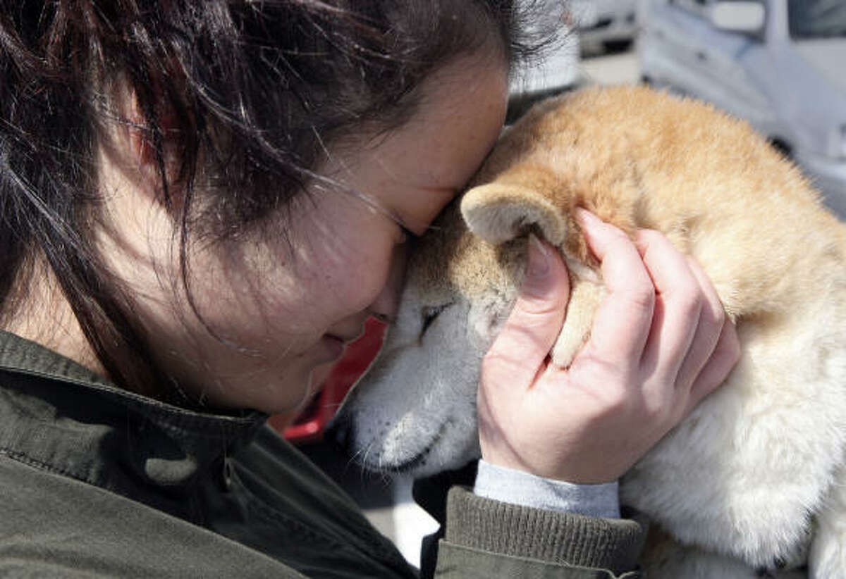 Shoko Igarashi, 17, hugs her dog before saying goodbye. Friends will look after it while she is in a shelter in Koriyama in Fukushima, Japan.