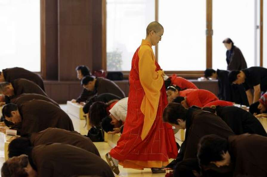 A Buddhist monk walks the aisle as devotees vow to pray during a prayer for Japanese earthquake vict
