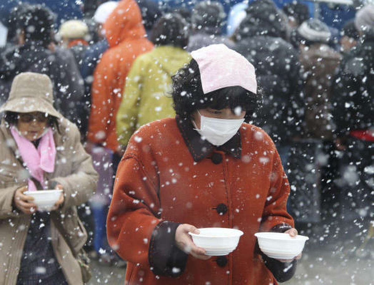 Evacuees carry bowls of pork soup from a soup kitchen back to their makeshift shelter in Minamisanriku, northern Japan, Wednesday, March 16, 2011, after Friday's earthquake and tsunami.