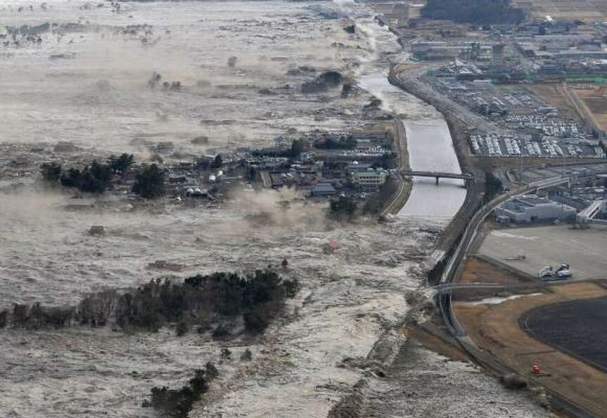 Earthquake-triggered tsunami waves sweep along Iwanuma in northern Japan. March 11, 2011.