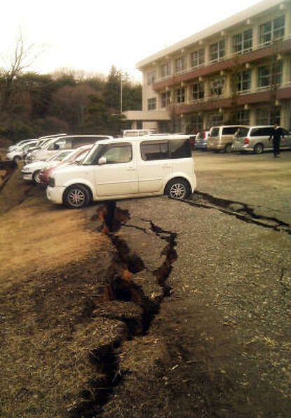 Vehicles straddles a damaged parking lot in Yabuki, in southern Fukushima prefecture. March 11, 2011