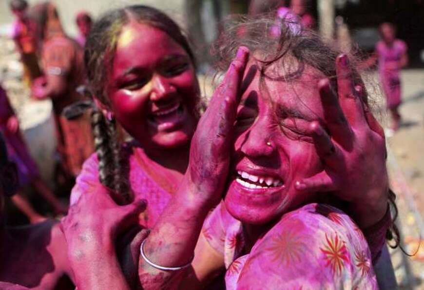 Indian girls smear each other's face with colored powder as they celebrate Holi in Mumbai, India.