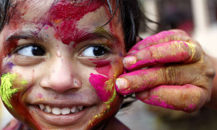 A young girl gets her face smeared with colored powder during Holi festival in Kuala Lumpur. Photo: Lai Seng Sin, AP