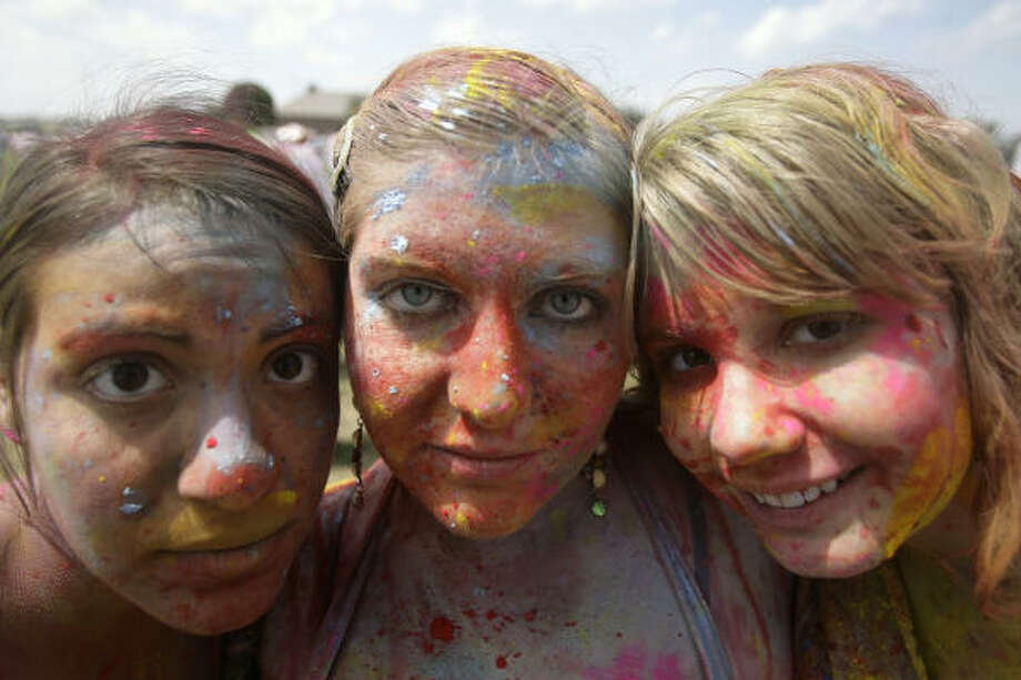 In Houston, Amelia Petrini, Amanda Castleberry and Alyxis Smith join the Holi Festival at Seabourne Creek Park Sunday. Photo: Cody Duty, Houston Chronicle