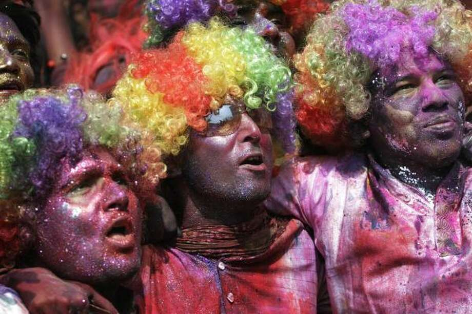 Indians even don colorful wigs to match their colored faces and clothing in Gauhati, India. Photo: Anupam Nath, AP