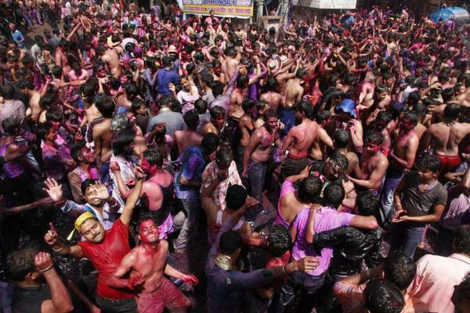 Indians dance after smearing their faces with color and throwing water in Allahabad, India. Photo: Rajesh Kumar Singh, AP