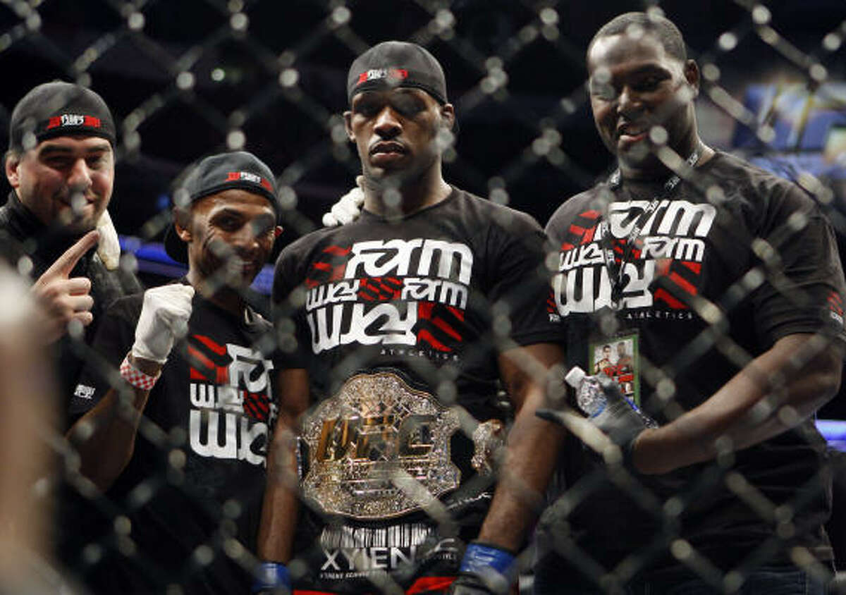Jon Jones, second from the right, stands with others while wearing a light heavyweight belt after defeating Mauricio Rua.