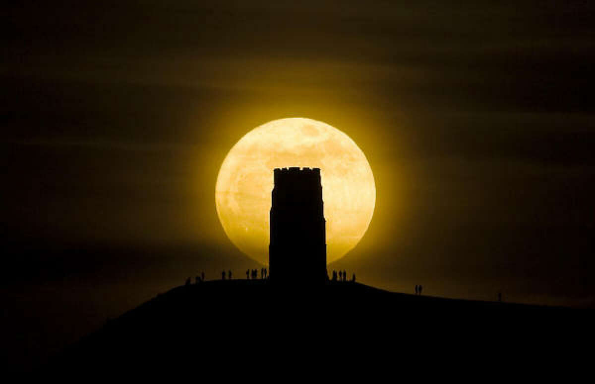 People stand beside St. Michael's Tower on Glastonbury Tor hill watching the moon as it progresses across the sky, at its closest point to the Earth for almost two decades.
