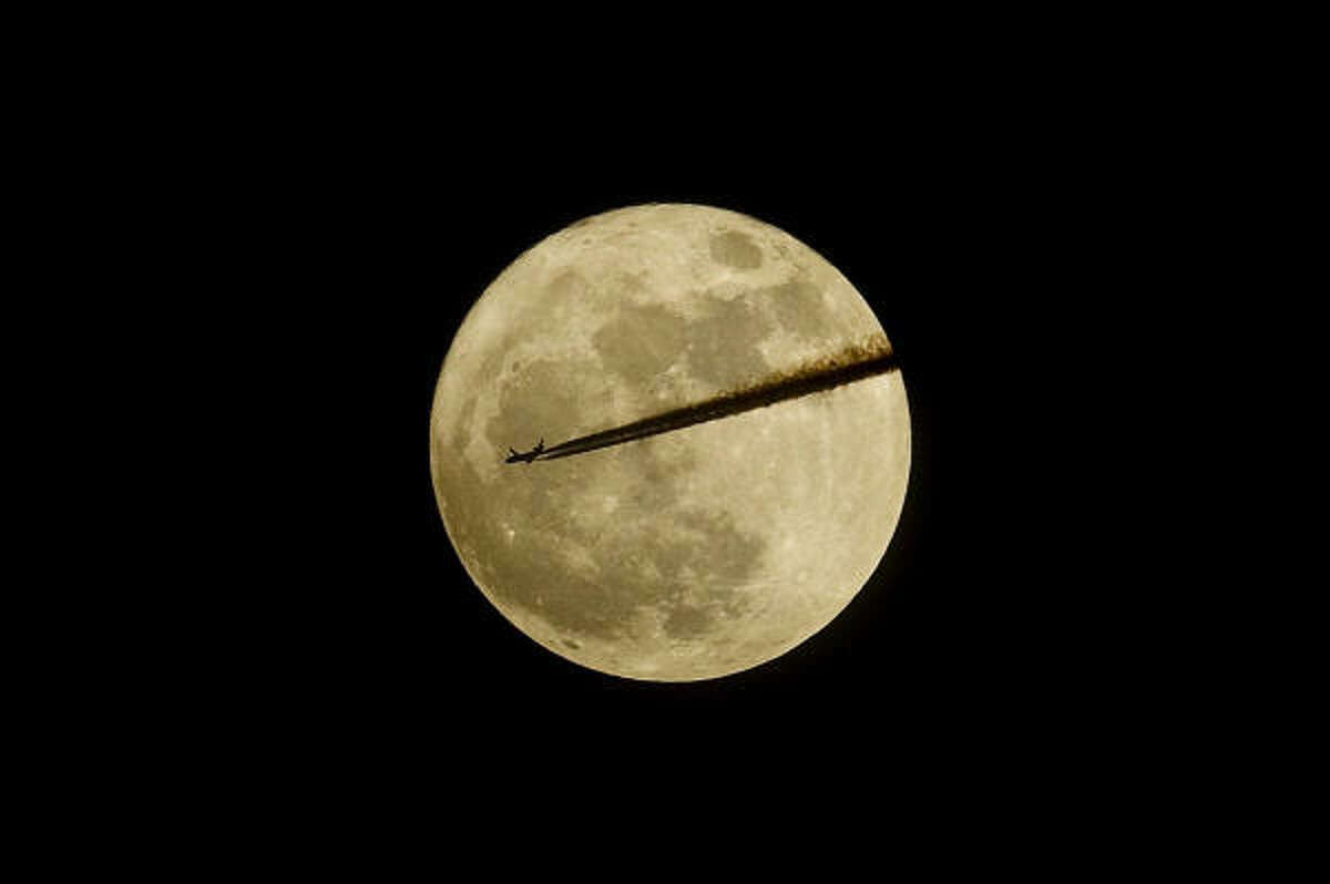 An aircraft flies past the moon as seen from Somerset in southern England as the moon is at its closest point to the Earth for almost two decades. It is the first time since Jan. 19, 1992 that the Moon has come into such close proximity to the Earth.