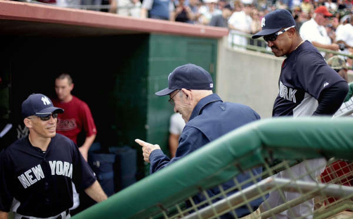 Yogi Berra, center, speaks with Yankees manager Joe Girardi, left, before the game against the Astrosin Kissimmee, Fla.