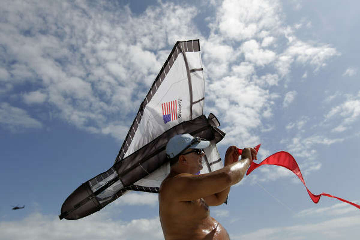 Joseph Foti, of Poinciana, Florida, tries to untangle his space shuttle kite on the beach at Jetty Park near Cape Canaveral as people gather to watch the last Discovery shuttle launch at Kennedy Space Center. Foti said,