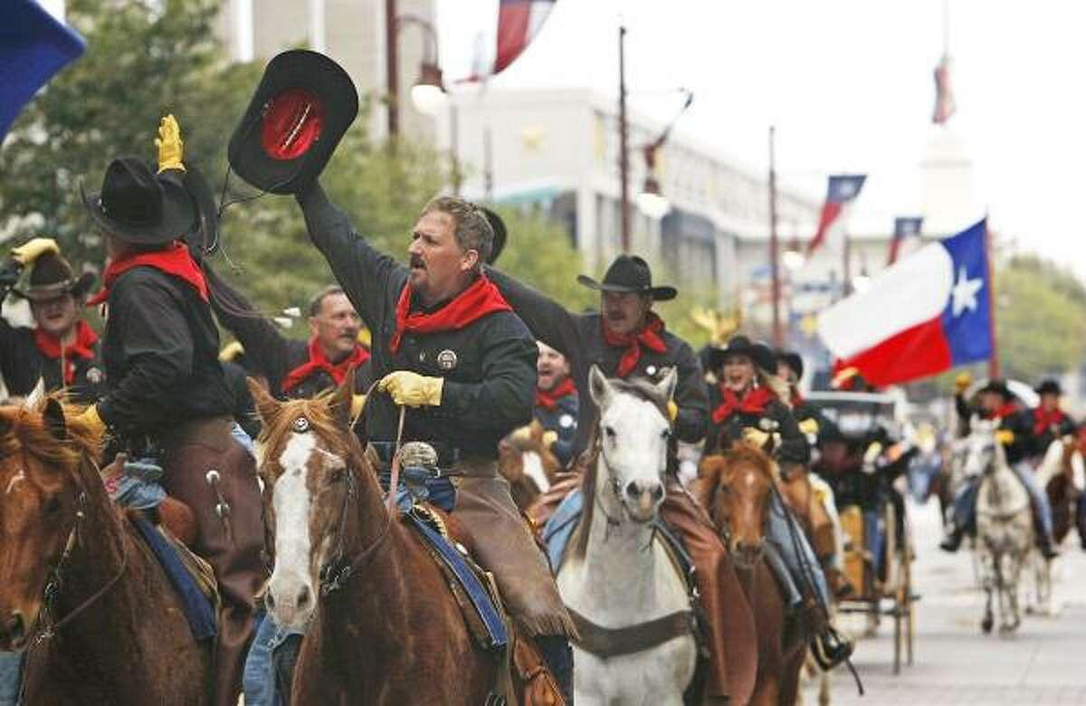 The Salt Grass Trail Ride Association's Desperados wave to the crowds.