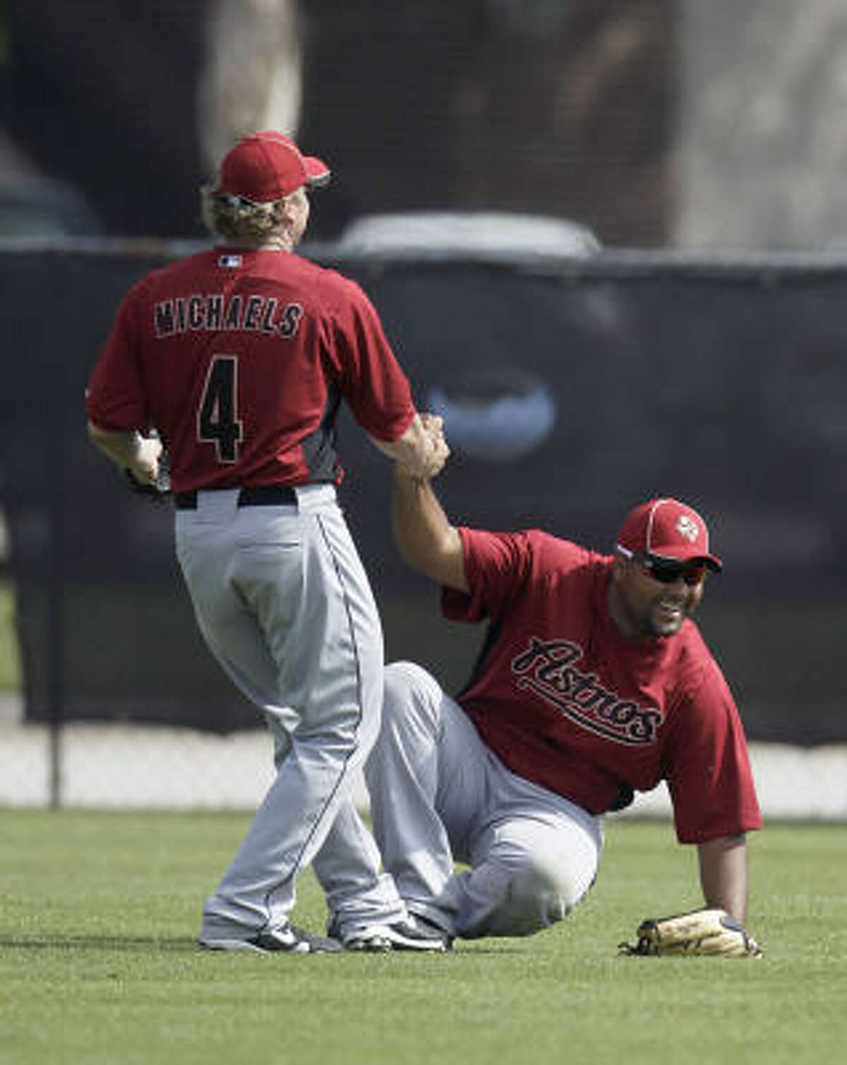 Outfielder Carlos Lee, right, gets helped up by Jason Michaels.