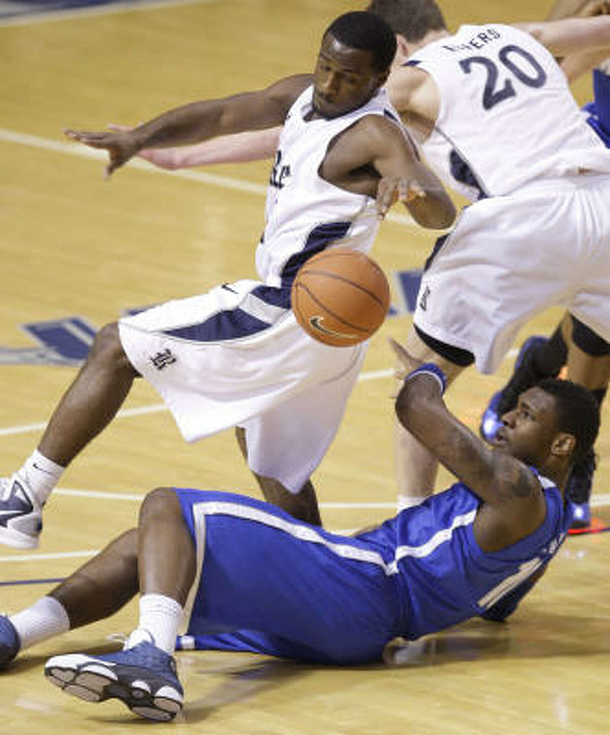 Rice's Bryan Beasley, left, and Lucas Kuipers (20) try to avoid stepping on Memphis' Tarik Black as they scramble for a loose ball during the first half.