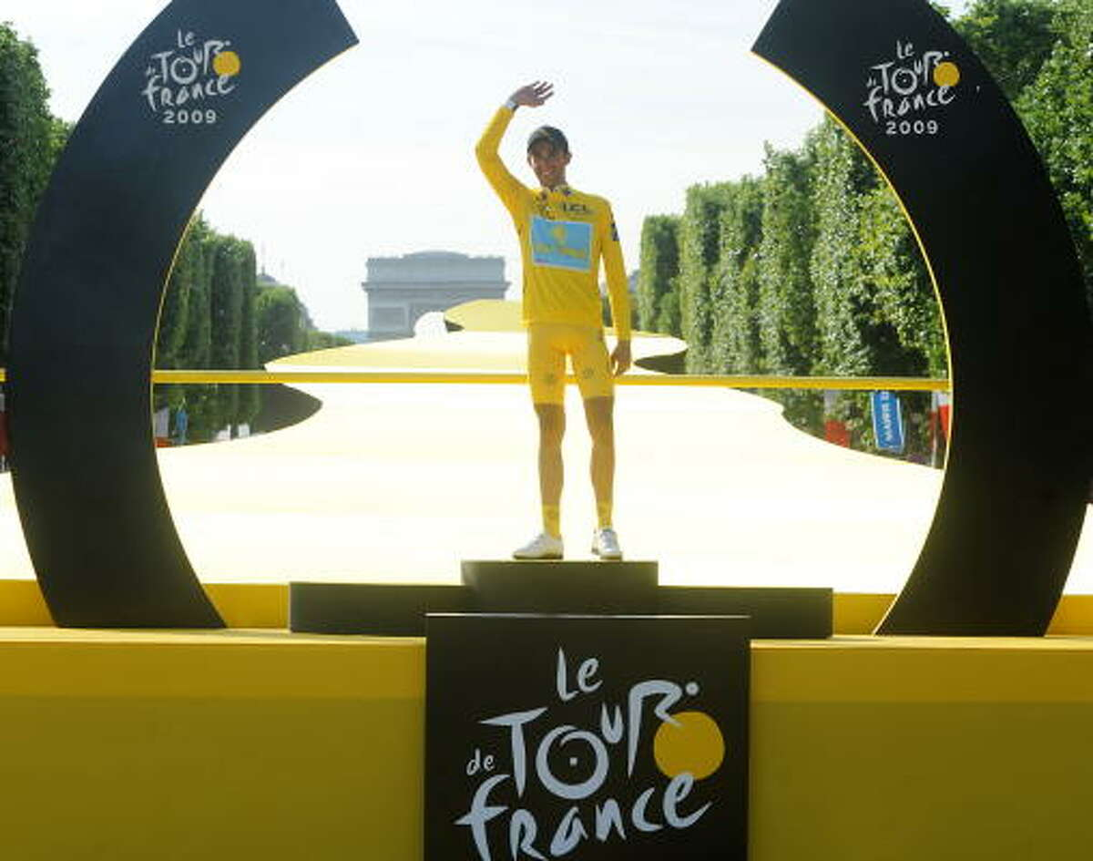 The winner of the 2009 Tour de France cycling race, Alberto Contador of Spain waves on the podium Sunday on the famous Champs-Elysees Avenue in Paris.
