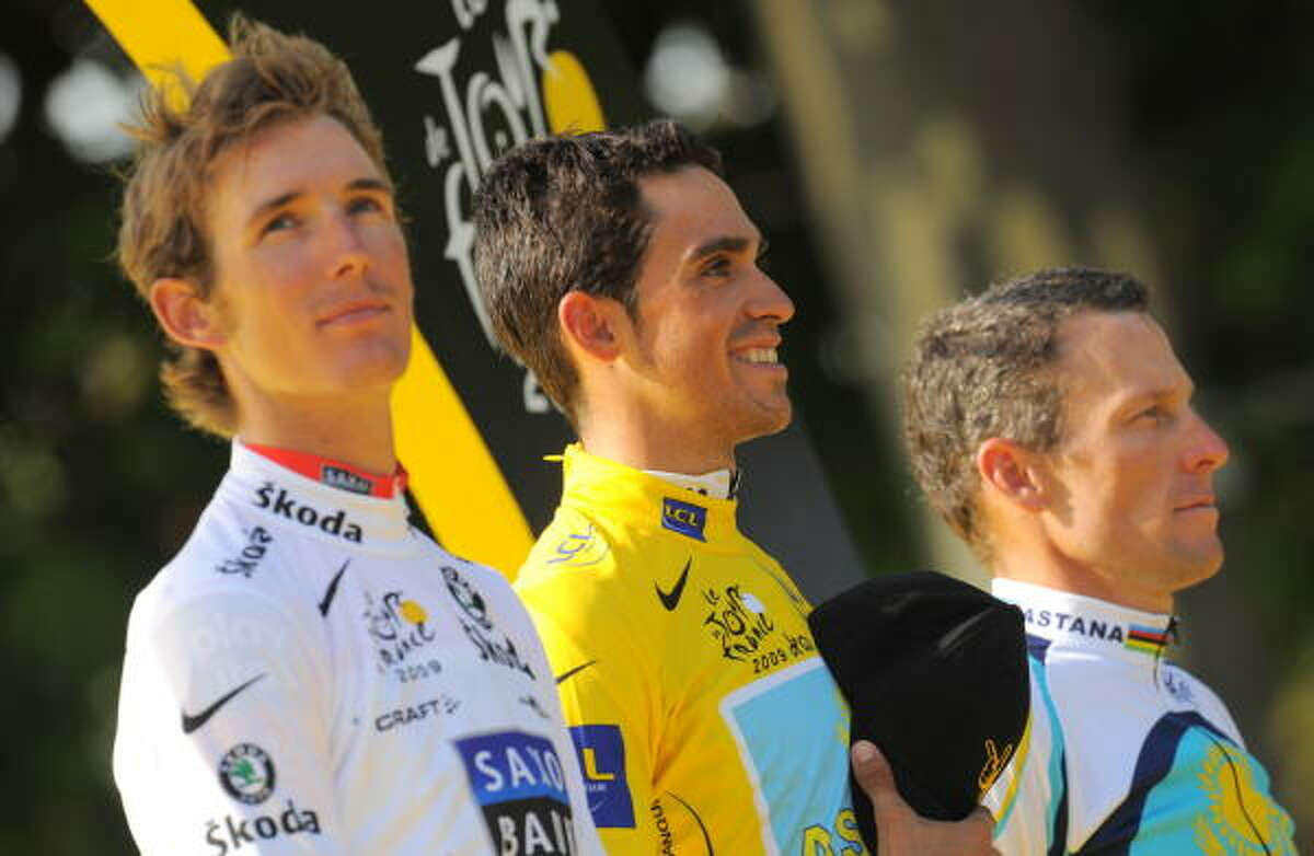 The winner of 2009 Tour de France cycling race, Alberto Contador of Spain, center, second-place finisher Andy Schleck of Luxemburg, left, and third-place finisher Lance Armstrong pose on the podium Sunday.