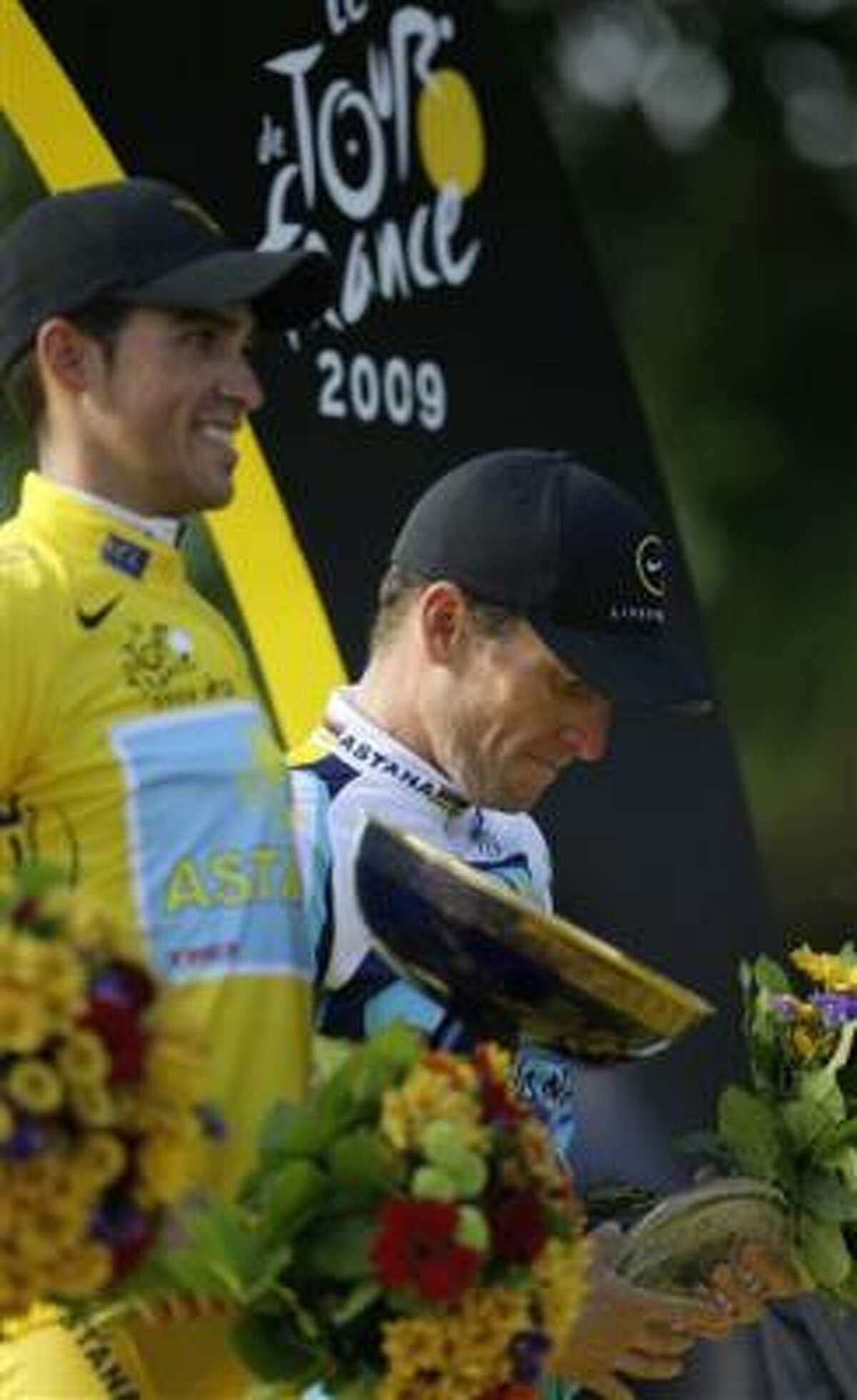 Tour de France winner Alberto Contador of Spain, wearing the overall leader's yellow jersey, left, and third-placed, seven-time Tour de France winner Lance Armstrong, react on the podium after the 21st stage of the Tour de France on Sunday.