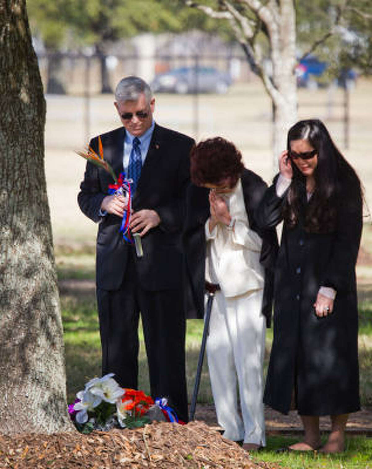 Johnson Space center director Michael L. Coats, left, stands with Lorena Onizaka and Darien Onizuka-Morgan, the wife and daughter of space shuttle Challenger astronaut Ellison Onizuka, after placing flowers on a memorial marker for Onizuka in the Astronaut Memorial Tree Grove during the annual National Day of Remembrance ceremony at the Johnson Space Center on Thursday, Jan. 27, 2011, in Houston. NASA holds the agency-wide Day of Remembrance every January to honor the fallen crews of Apollo 1and space shuttles Challenger and Columbia.