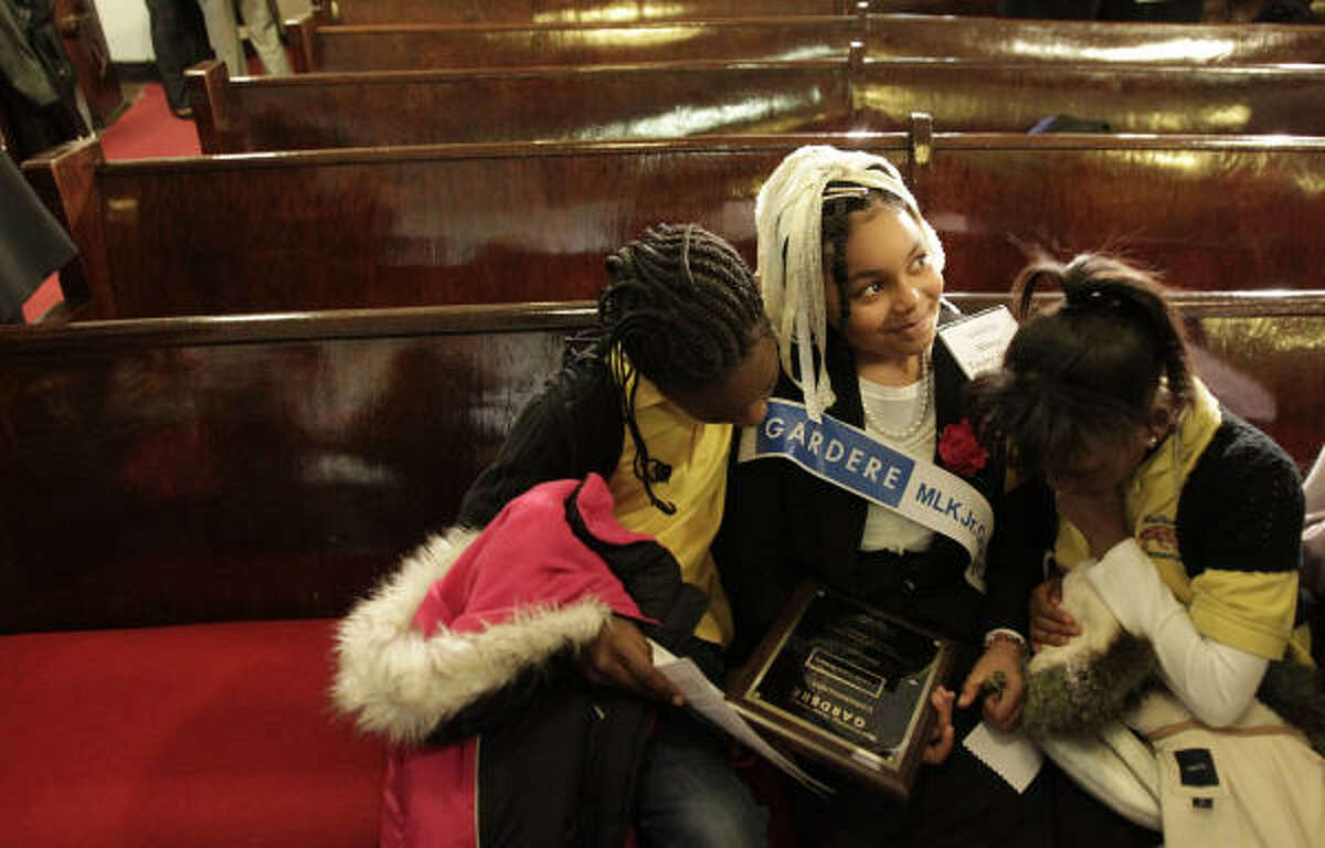 Miesha Walker looks at Ahnia Leary-Haley's participation plaque along with Destiny Johnson after the the 12 HISD students delivered presentations in the 15th Annual Gardere Martin Luther King. Jr. Oratory Competition at Antioch Missionary Baptist Church of Christ on Friday, Jan. 14, 2011, in Houston.