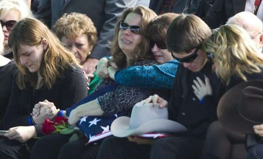 Melissa Norsworthy, center, grieves with her children, Katlyn, left, and Jacob during the funeral for her husband of Fort Bend County Sheriff's Deputy John David Norsworthy, Jr., Saturday, Jan. 8, 2011, in Rosenberg. The deputy died Tuesday, a week after he crashed his squad car in the line of duty. Photo: Brett Coomer, Houston Chronicle