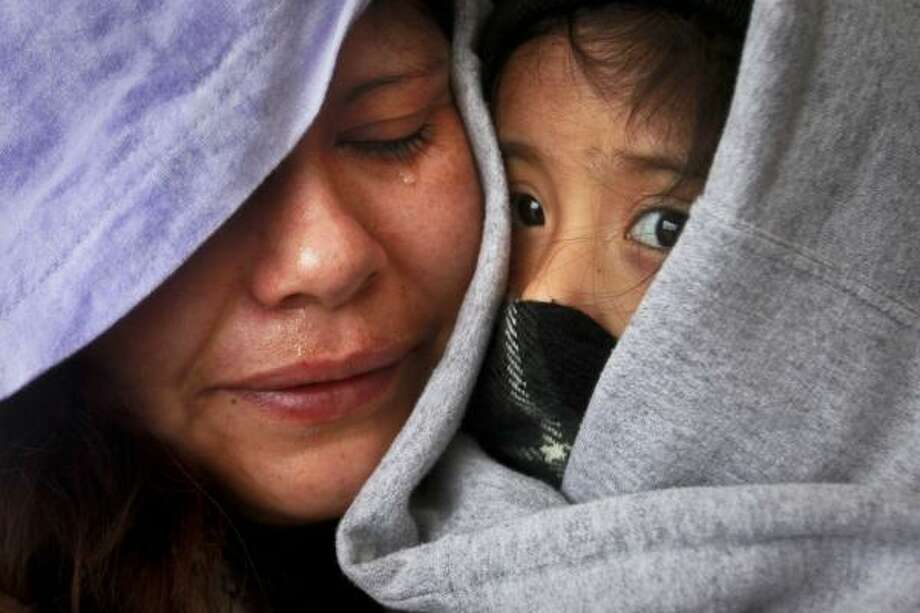 "With tears in her eyes, Reyna Martinez held her four-year-old daughter Emily in a bus shelter saying ""it's too cold"" as she was trying to take her daughter to the Harris County Hospital District's Casa de Amigos Health Center on the 1600 block of N. Main, however the facility opened an hour later than she anticipated Wednesday. Photo: Johnny Hanson, Houston Chronicle"
