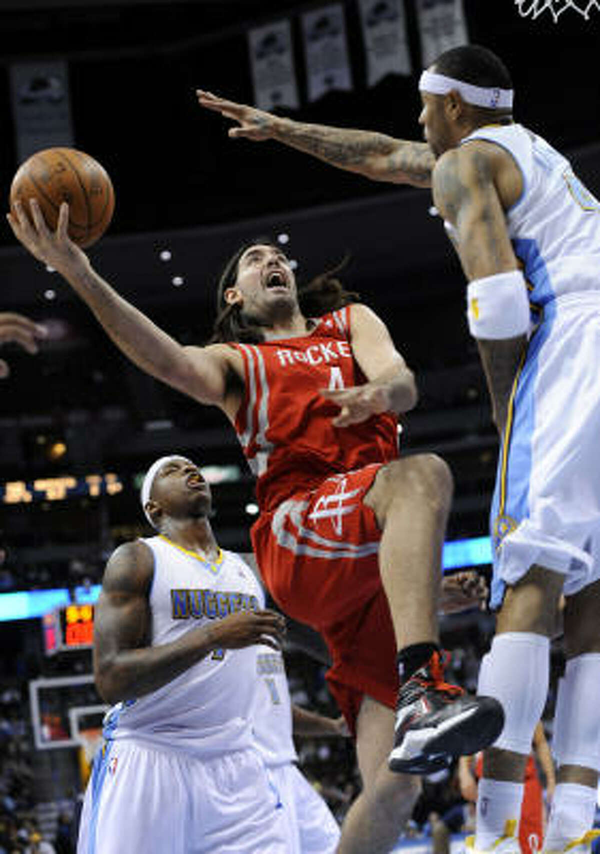 Rockets forward Luis Scola (4) goes up for a shot against Nuggets forward Kenyon Martin (4) as Al Harrington (7) watches the play.