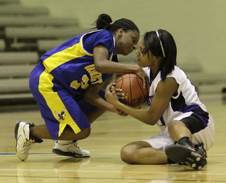 Washington's Cherelle Polk (21) battles with Wheatley's Ariel Taylor (11) for a loose ball. Wheatley won the game 72-53. Photo: Karen Warren, Chronicle