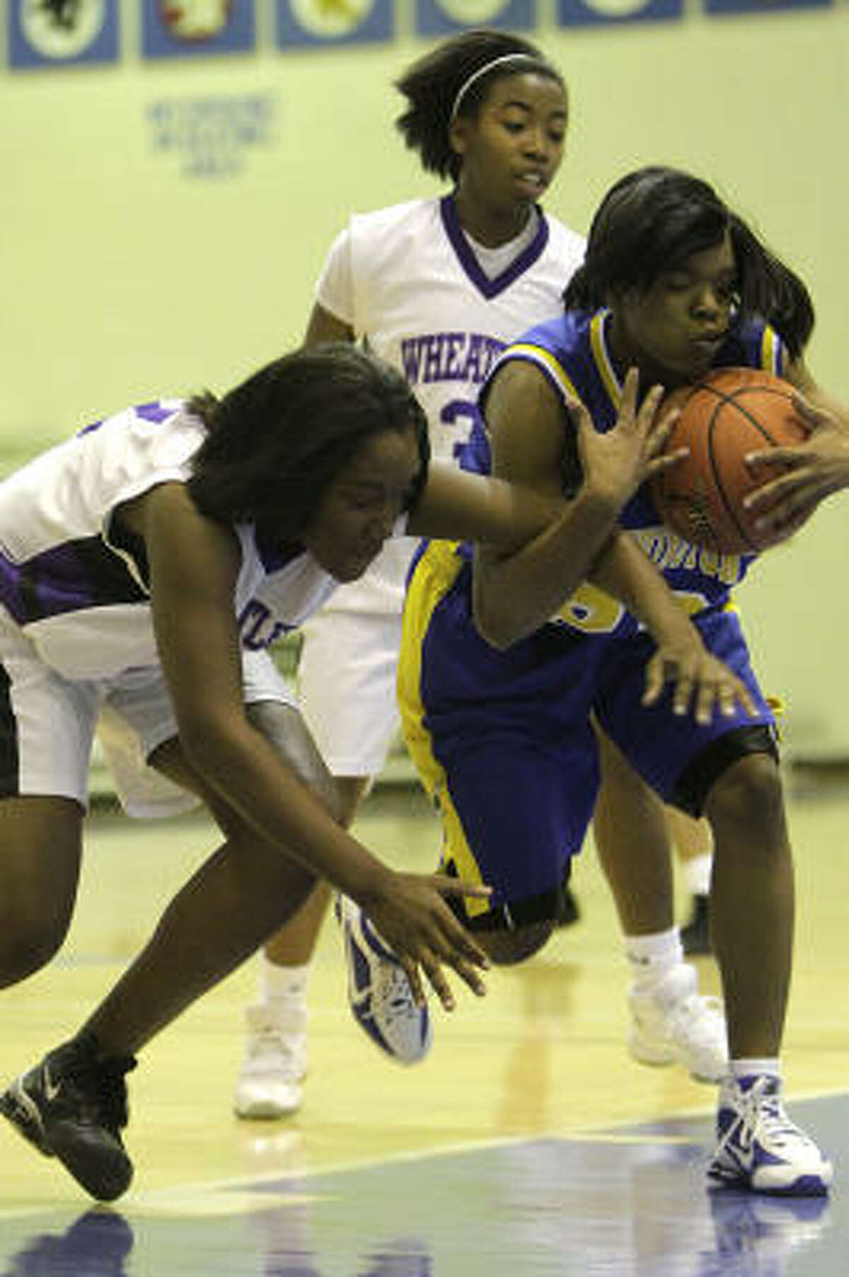 Washington's Candace Collins (23) battles for control of the ball with Wheatley's Jordoniee Wilson (32).