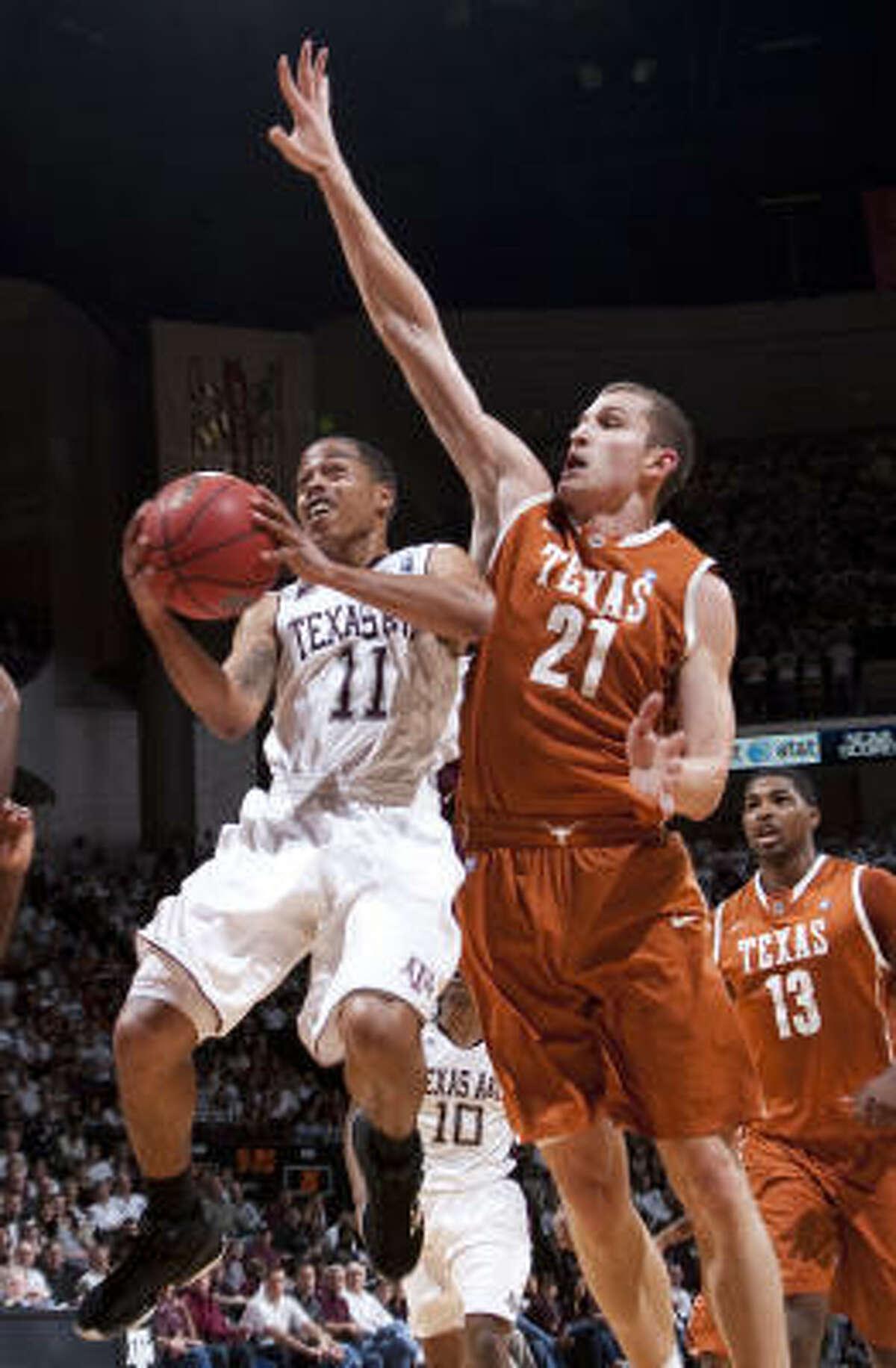 Texas A&M guard B.J. Homes (11) goes for a shot against Texas' Matt Hill (21).