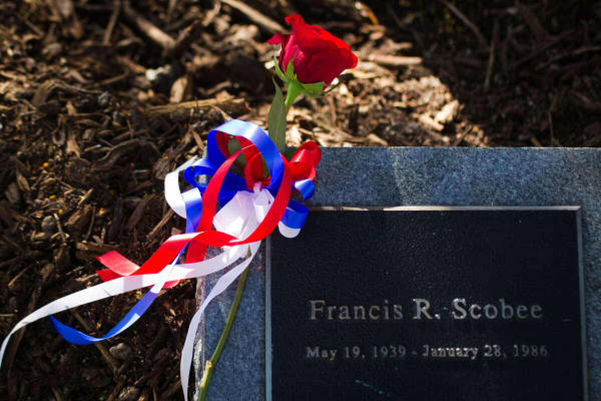 A red rose rests on a marker for space shuttle Challenger commander Francis R.